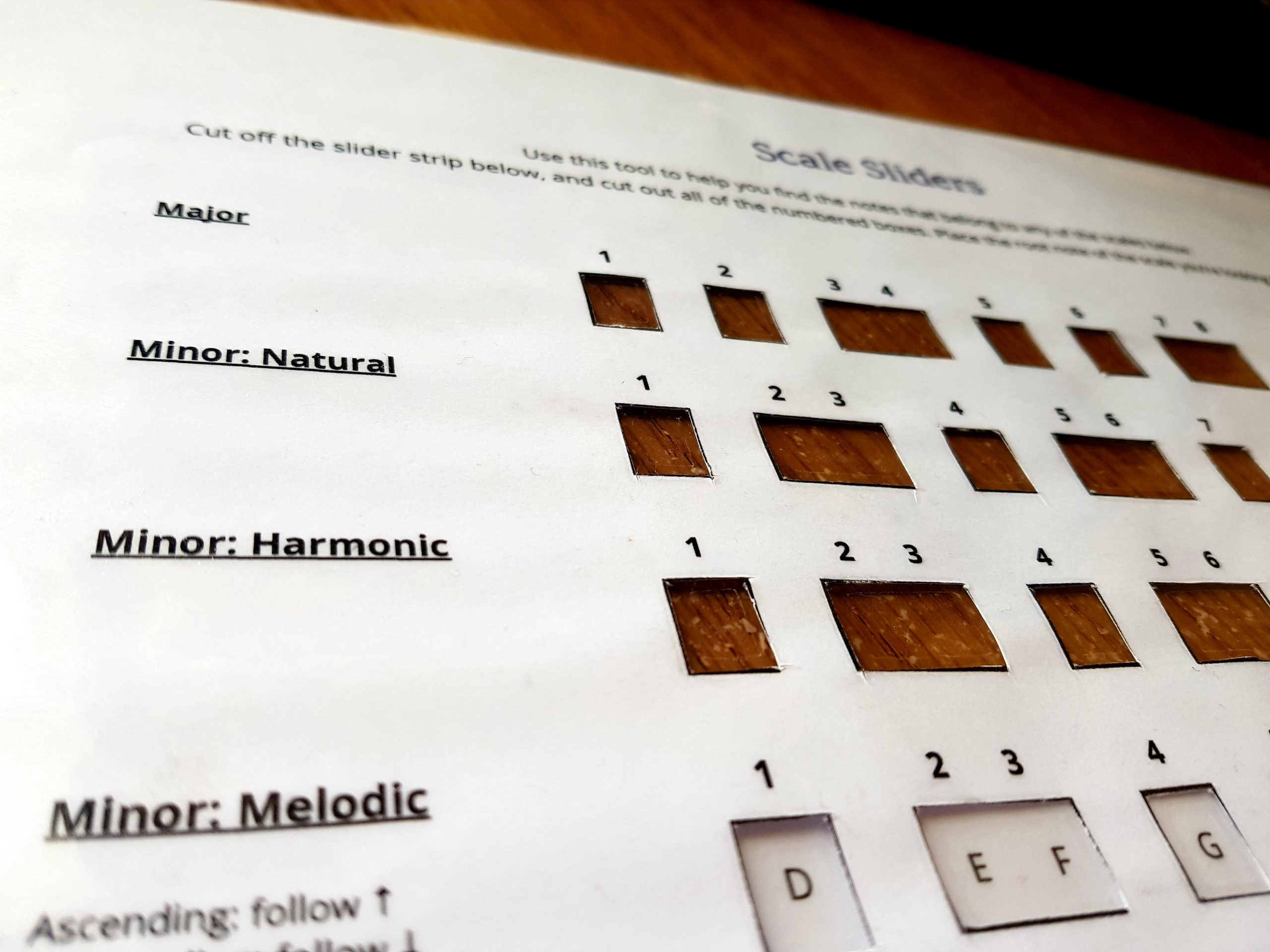Image of printed scale sliders for non-pianists, with windows cut out to show the notes of each type of scale.